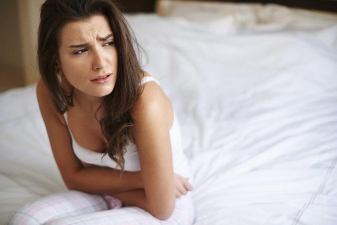 Frau sitzt mit schmerzverzerrtem Gesicht auf dem Bett