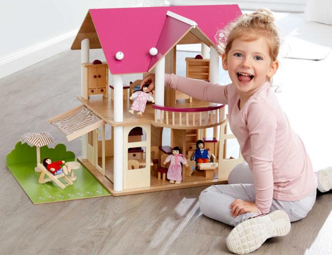 Mädchen spielt mit Puppenhaus aus Holz