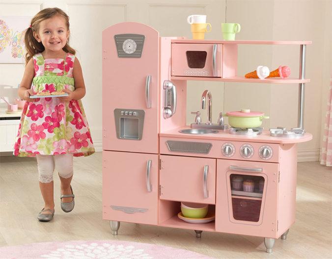 Mädchen spielt in rosa Retroküche