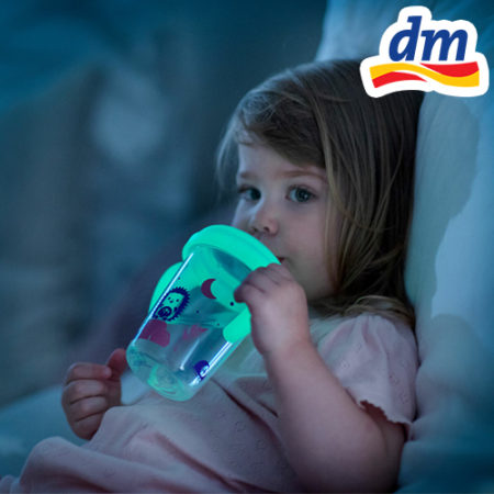 Kind mit leuchtender Trinklernflasche
