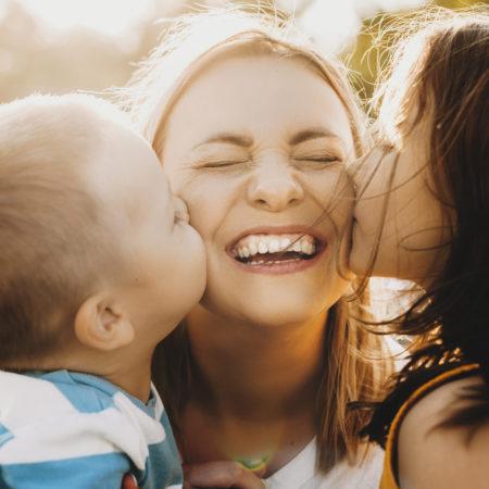 Kinder küssen Mutter auf die Wange