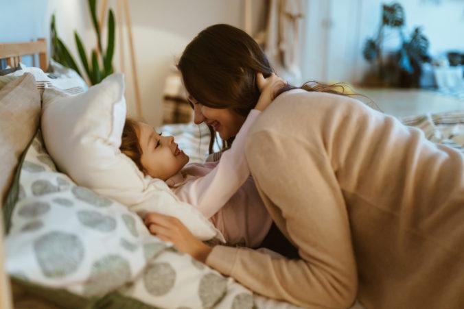 Mutter kuschelt mit Kind im Bett