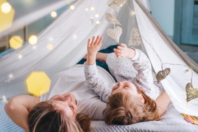 Mutter und kleine Tochter liegen unter Tipi
