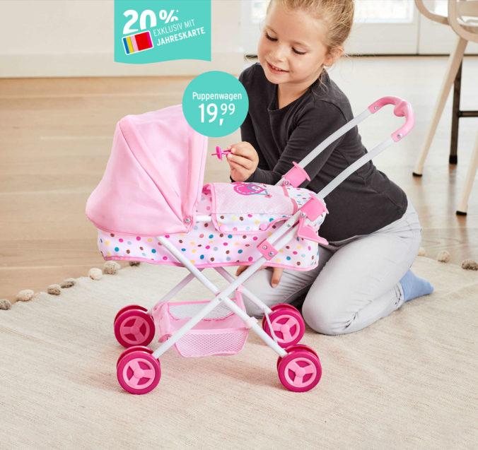 Mädchen spielt mit Puppenwagen