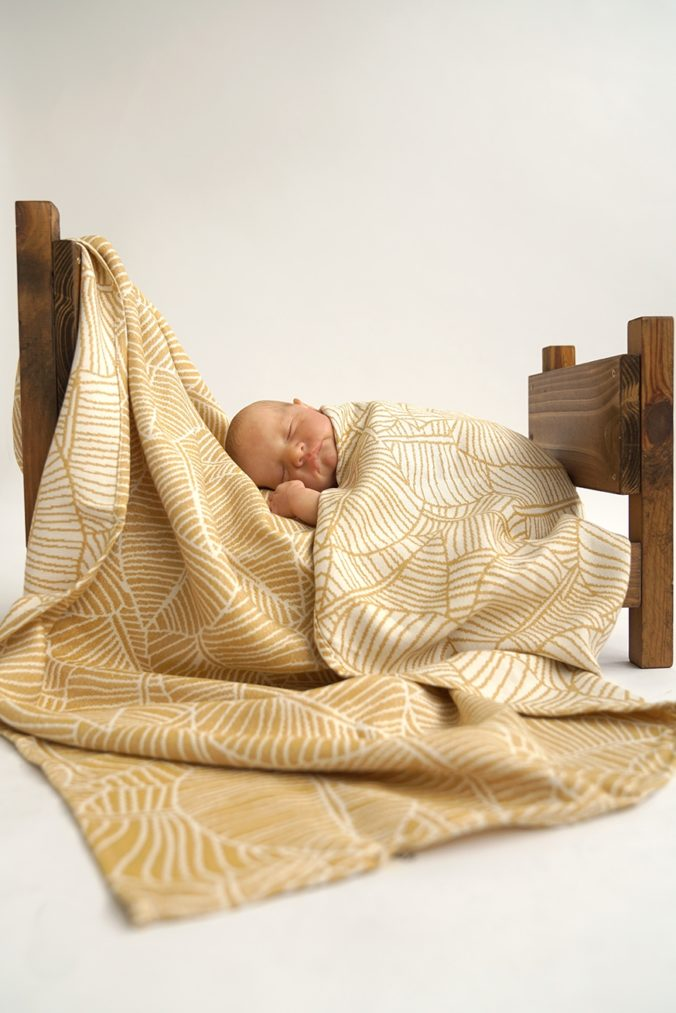 Baby eingekuschelt in gelber Babydecke