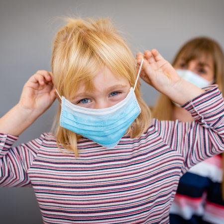 Kleines Mädchen setzt sich Maske auf