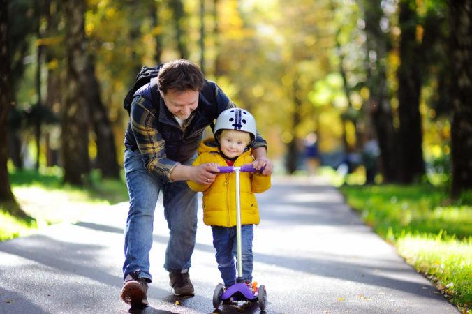 Vater übt mit Kind rollerfahren im Park