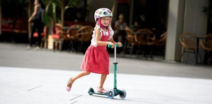 Kleines Mädchen mit Cityroller