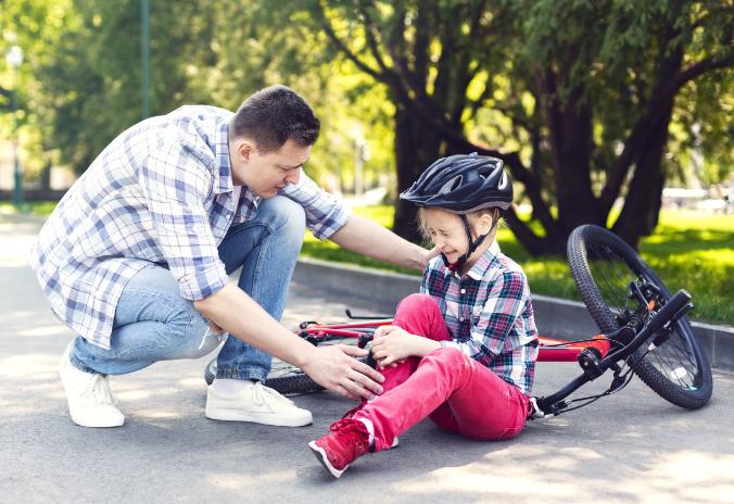 Vater tröstet Kind nach Sturz mit dem Fahrrad