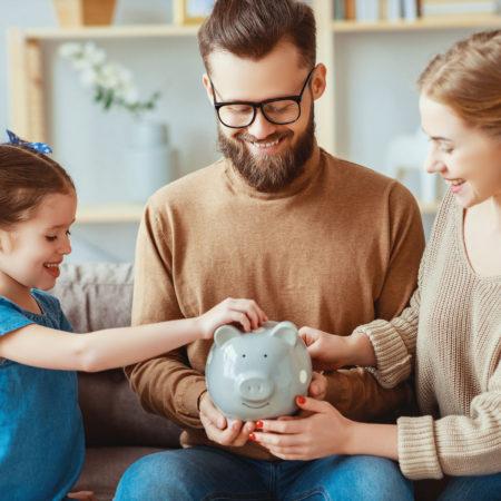 Familie steckt Geld in Sparschwein
