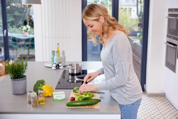 Schwangere Frau schneidet Gemüse in der Küche