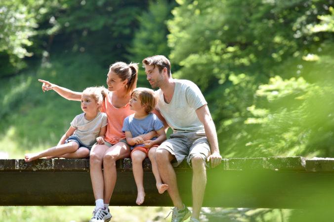 Familie sitzt auf einer Brücke